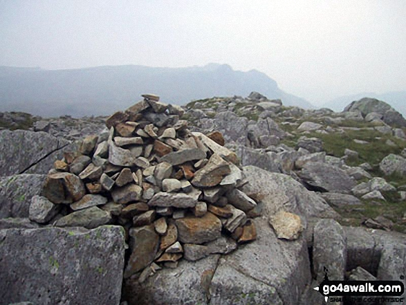 Rossett Pike summit cairn with The Langdale Pikes in the distance