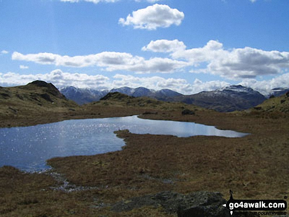 Looking across an unnamed tarn below Great Castle How to Wetherlam and the Furness Fells