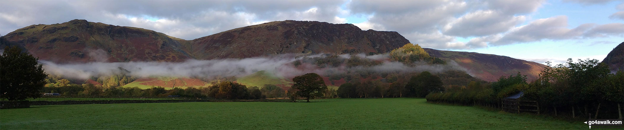 Walk c369 High Raise, Ullscarf and Grange Fell from Rosthwaite - Early morning valley mist below Dale Head (Newlands) and High Spy, Maiden Moor & Cat Bells (Catbells) with the summit of Castle Crag (front right) lit by a ray of sunshine from Rosthwaite