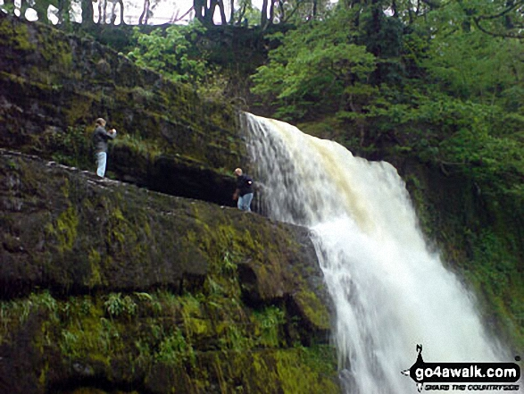 Two guys taking a chance at Sgwd yr Elra Waterfall, Afon Mellte in the background