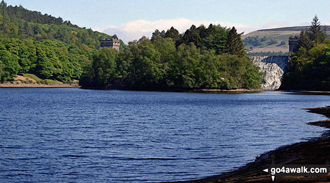 Island Plantation in the middle of Derwent Reservoir with water cascading over Howden Reservoir Dam beyond