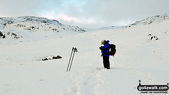 Checking the GPS on Sty Head in the snow. Walk route map c454 Scafell Pike via The Corridor Route from Seathwaite photo
