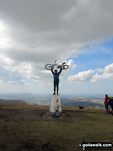 Cyclist (and bike) on The Calf trig point