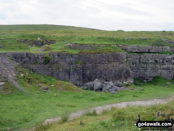 An old quarry with Faulds Brow summit on the horizon