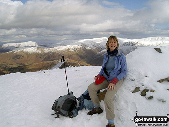 Sitting on Dove Crag summit cairn in the snow. Walk route map c247 The Fairfield Horseshoe from Ambleside photo