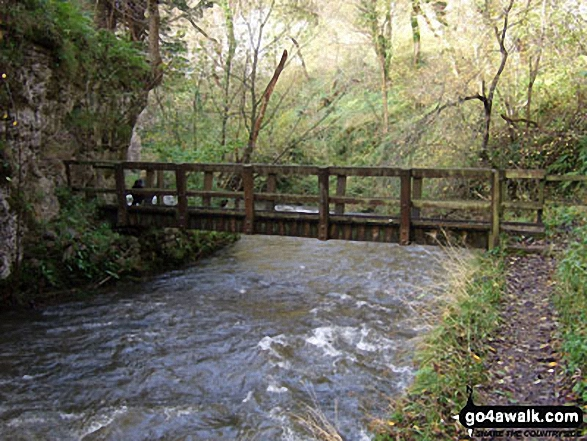 The Monsal Trail crossing a footbridge over The River Wye in Chee Dale