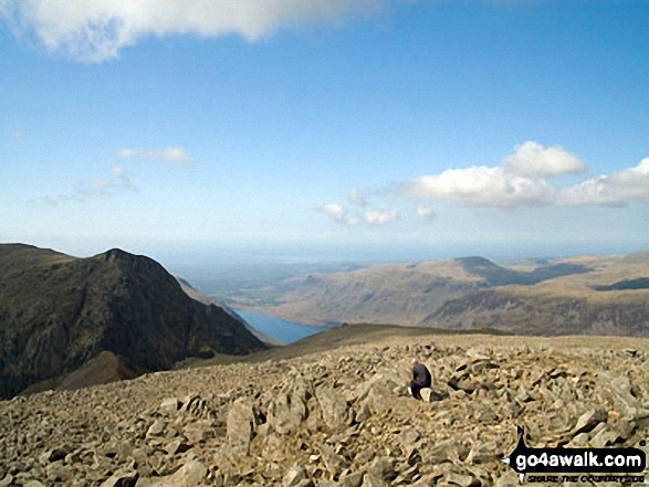 Lone fell walker on Scafell Pike with Symonds Knott and Sca Fell (left), Wast Water and Seatallen (right) beyond. Walk route map c166 The Scafell Masiff from Wha House Farm, Eskdale photo