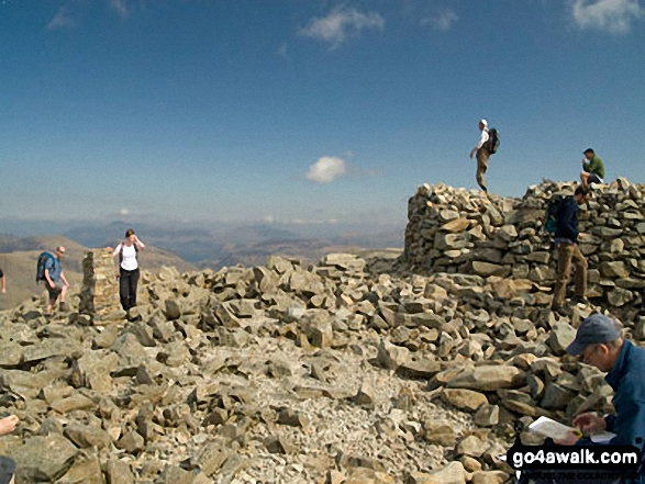 Holding on to the Trig point on Scafell Pike summit. Walk route map c370 Scafell Pike from Seathwaite photo