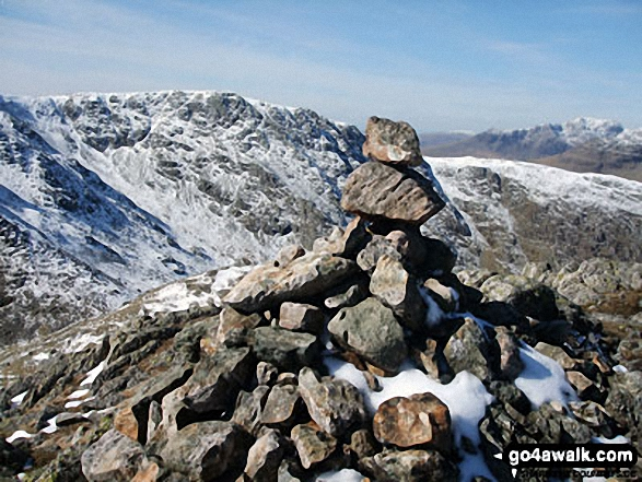 Snow on Black Sails summit cairn with Great Carrs (centre left) and Scafell Pike (far right) in the background