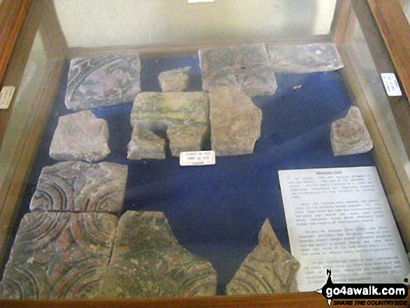 Display case containing medieval tiles inside St. Bartholomew's Church, Blore