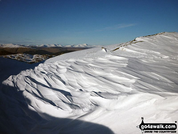 Snow scultured by the wind with the The Lawers range in the distance from Ben Ledi