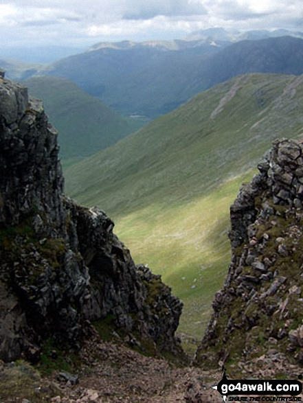 View down a steep gully from the summit of Sgor na h-Ulaidh Ben Nevis is on the horizon - just right of centre
