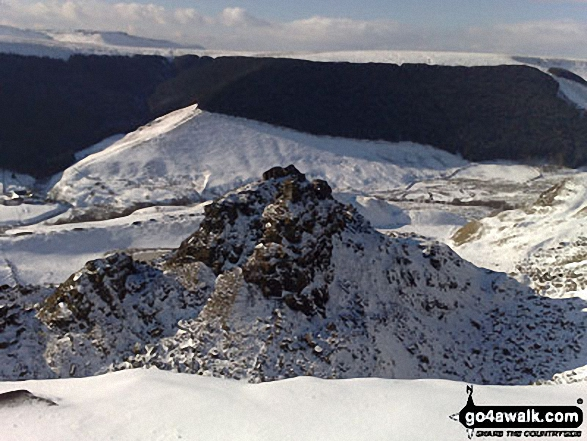 The Tower at Alport Castles in the snow with Kinder Scout in the background
