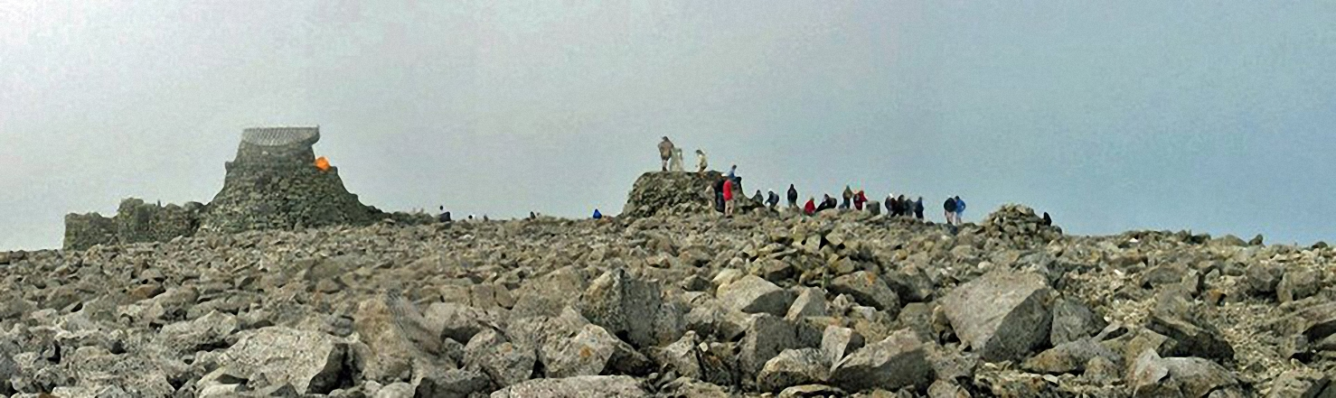 My daughter and friend, climbing up the summit cairn at the top of Ben Nevis