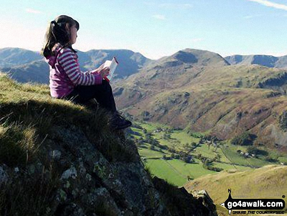 My daughter taking in the wise words of Wainwright on Angletarn Pikes