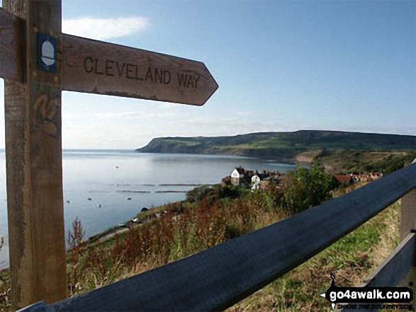 Cleveland Way National Trail sign at Robin Hood's Bay, with Ravenscar beyond