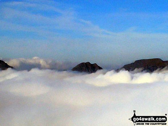 The Glyderau (Glyders) (left), Tryfan and Carrnedd Dafydd (The Carneddau) poking through low cloud from the summit of Carnedd Moel Siabod