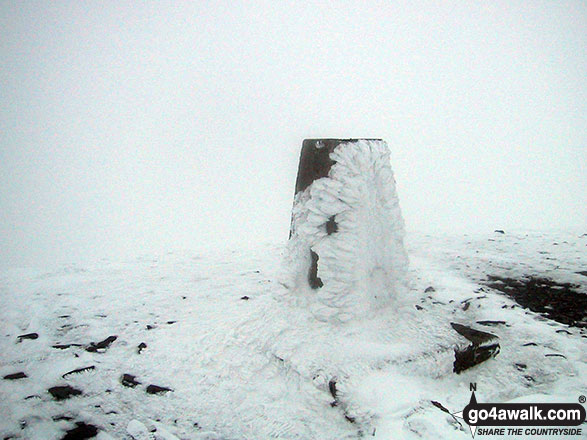 The trig point on the summit of a very cold and snowy Skiddaw