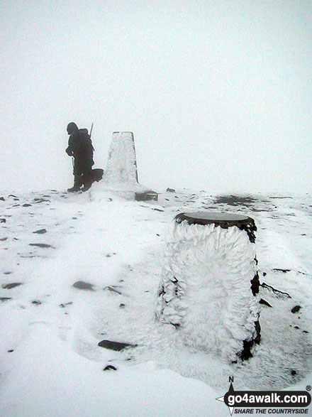 The trig point and viewpoint indicator on the summit of a very cold and snowy Skiddaw