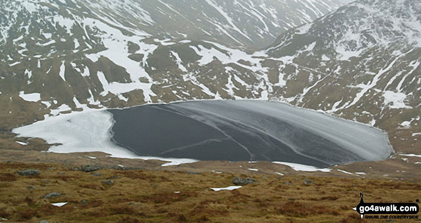 A frozen Grisedale Tarn from the lower slopes of Dollywaggon Pike in the snow