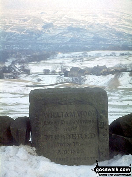 The 'Murder Stone' near Disley - with a snowy New Mills in the background
