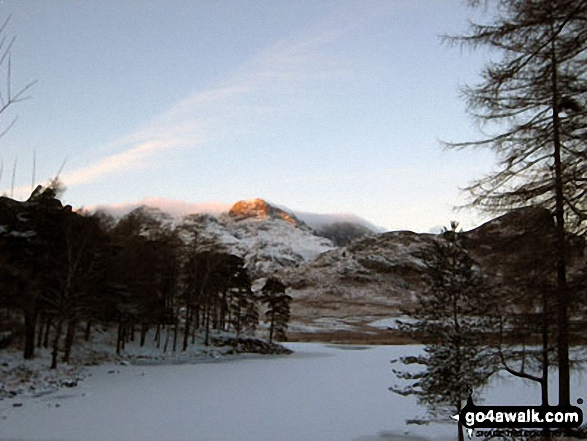 The last rays on sunshine on The Langdale Pikes across a frozen Blea Tarn (Langdale)