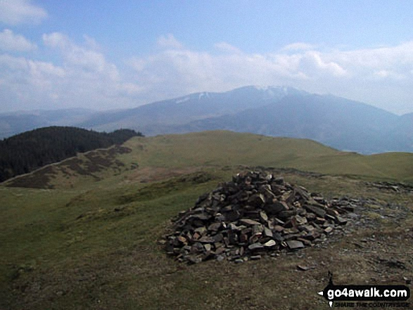 Sale Fell summit cairn with a snow topped Skiddaw looming in the distance