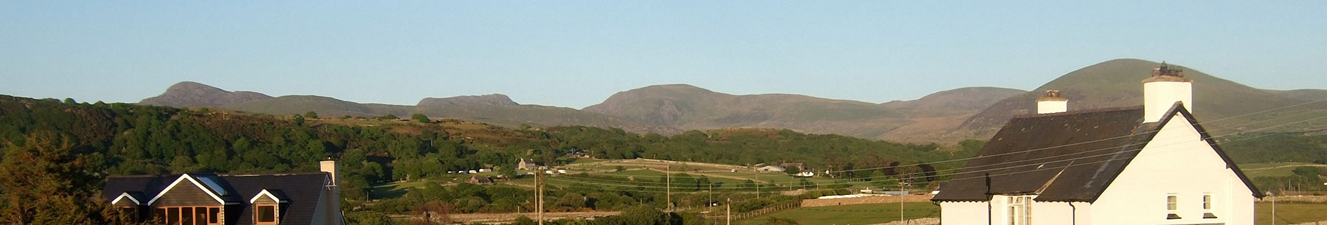 The Rhinogs featuring (left to right): Rhinog Fawr, Rhinog Fach, Y Llethr, Diffwys and Moelfre (Rhinogs) (behind the house) from Llandanwg