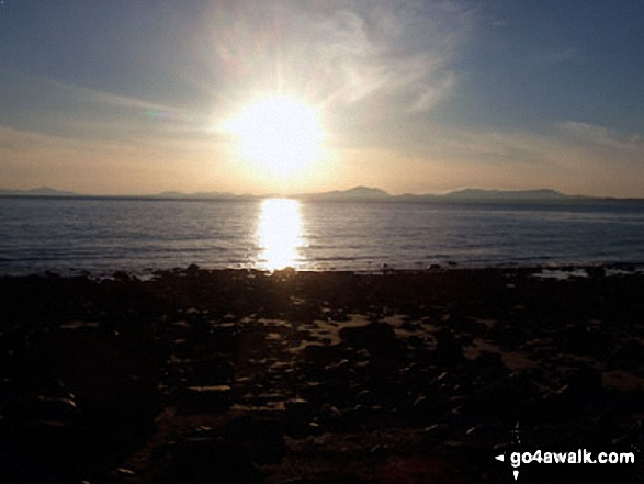 The sun setting behind the hills of The Lleyn Peninsula across Tremadog Bay from Llandanwg