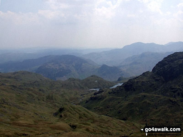 The view from Sergeant Man featuring Blea Rigg (centre left),Lingmoor Fell (distance centre), Stickle Tarn (partially hidden) and the shoulder of Pavey Ark (The Langdale Pikes) (right)