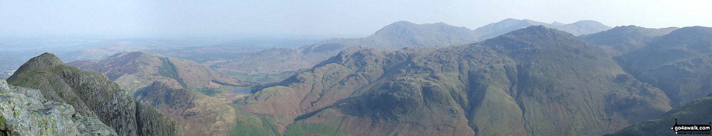 Loft Crag (foreground far left), Lingmoor, Blea Tarn, Pike of Blisco (Pike o' Blisco), Cold Pike and Crinkle Crags (featuring Crinkle Crags (South Top), Crinkle Crags (Long Top) and Gunson Knott) (mid-distance left to right) and Wetherlam, Great Carrs and Grey Friar (far-distance centre to right)  from the summit of Pike of Stickle (Langdale Pikes)