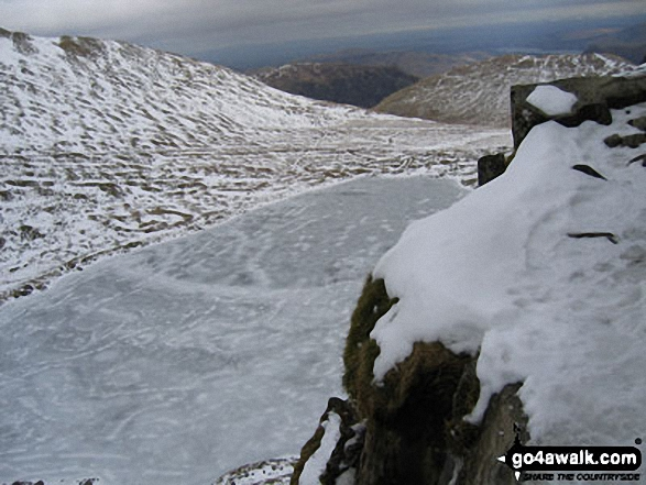 A Frozen Red Tarn from Striding Edge in the Snow. Walk route map c220 Helvellyn via Striding Edge from Glenridding photo