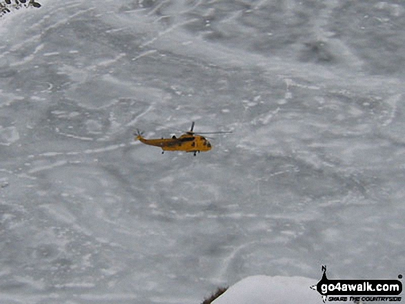 Rescue Helicopter above a frozen Red Tarn from Striding Edge. Walk route map c220 Helvellyn via Striding Edge from Glenridding photo
